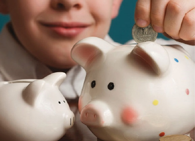 Youth putting a coin into piggy bank