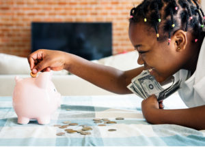 girl putting money in piggy bank
