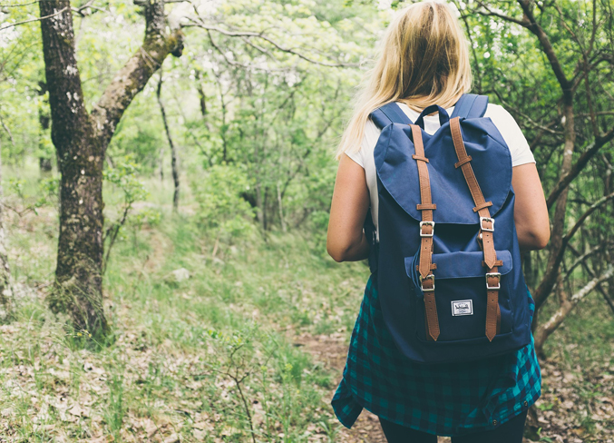 girl wearing a backpack hiking in the woods