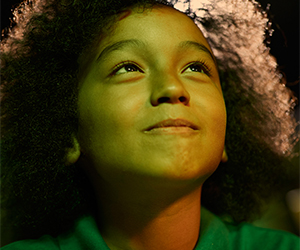 young boy with curly hair looking up