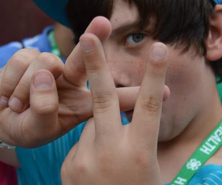4-H'er making a 4-H symbol with his hands