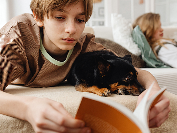 A young boy reading while cuddling with his dog