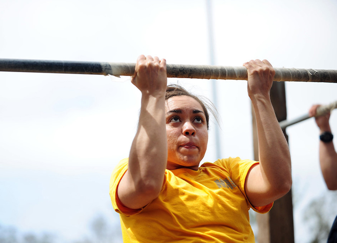 A girl doing a pull-up on a bar