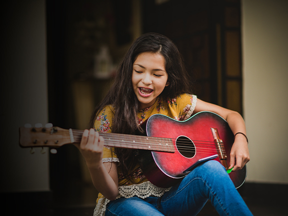 Young girl playing the acoustic guitar